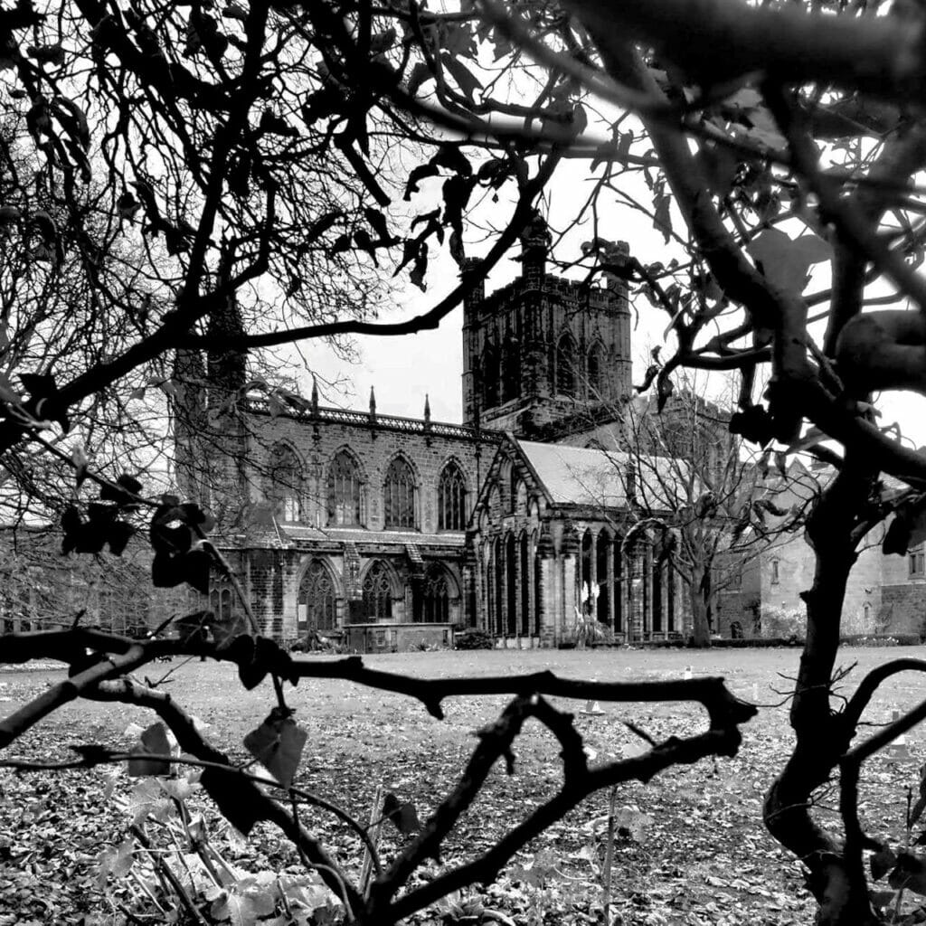 Black and white photo of Chester Cathedral through the trees.