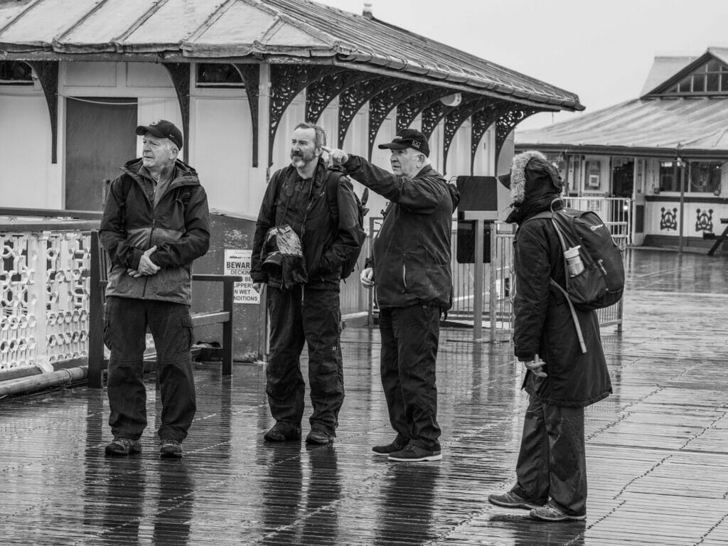 Black and White Photo of Eifion Williams from the Welshot Photographic Academy pointing out some of the landmarks from the Llandudno Pier in North Wales