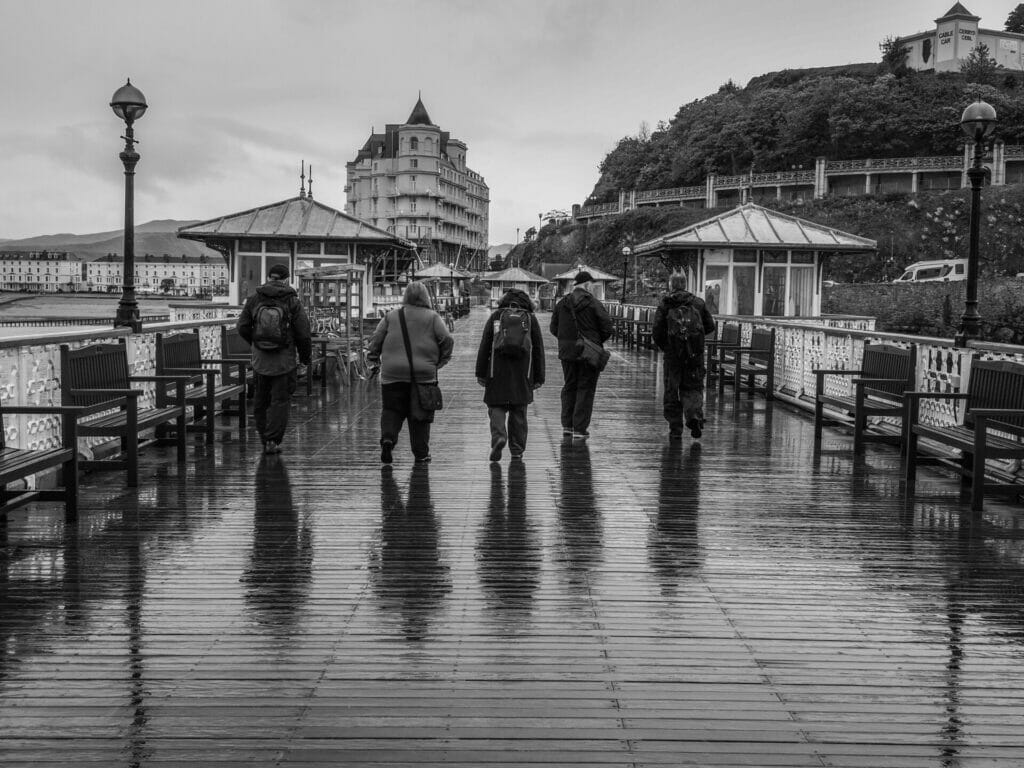 Black and White Photo of five photographers from the Welshot Photographic Academy walking along the Llandudno pier in the wet and rain after a photo workshop