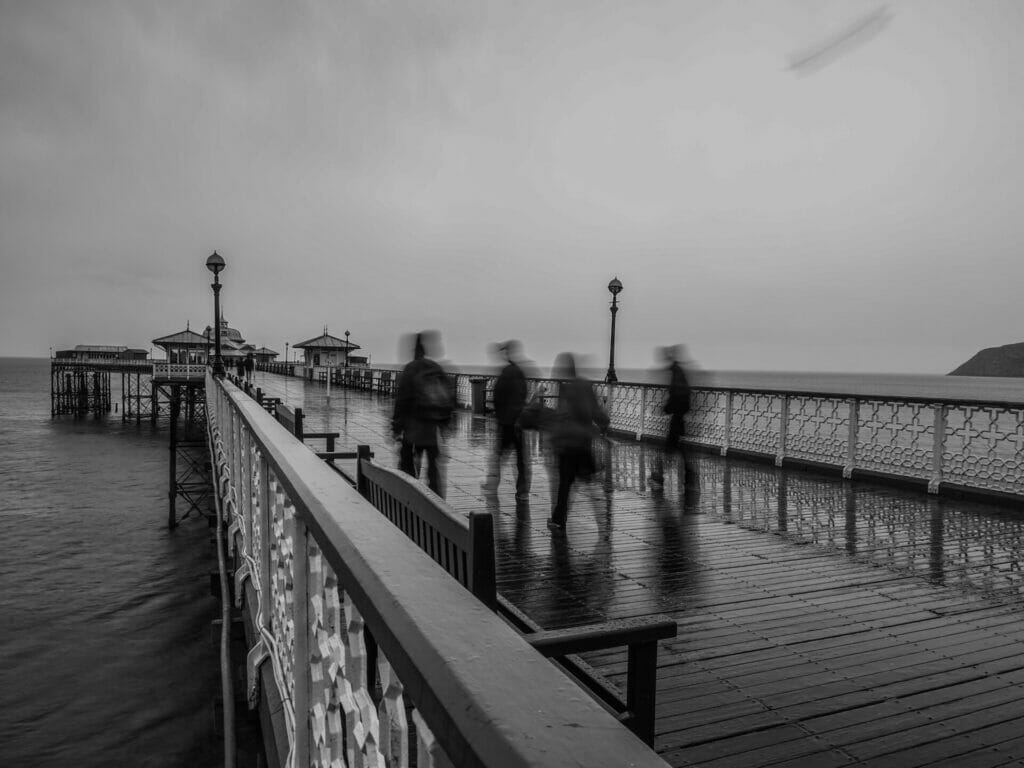 Black and White Photo of four photographers (blurred) being captured moving while walking along the Llandudno Pier in North Wales