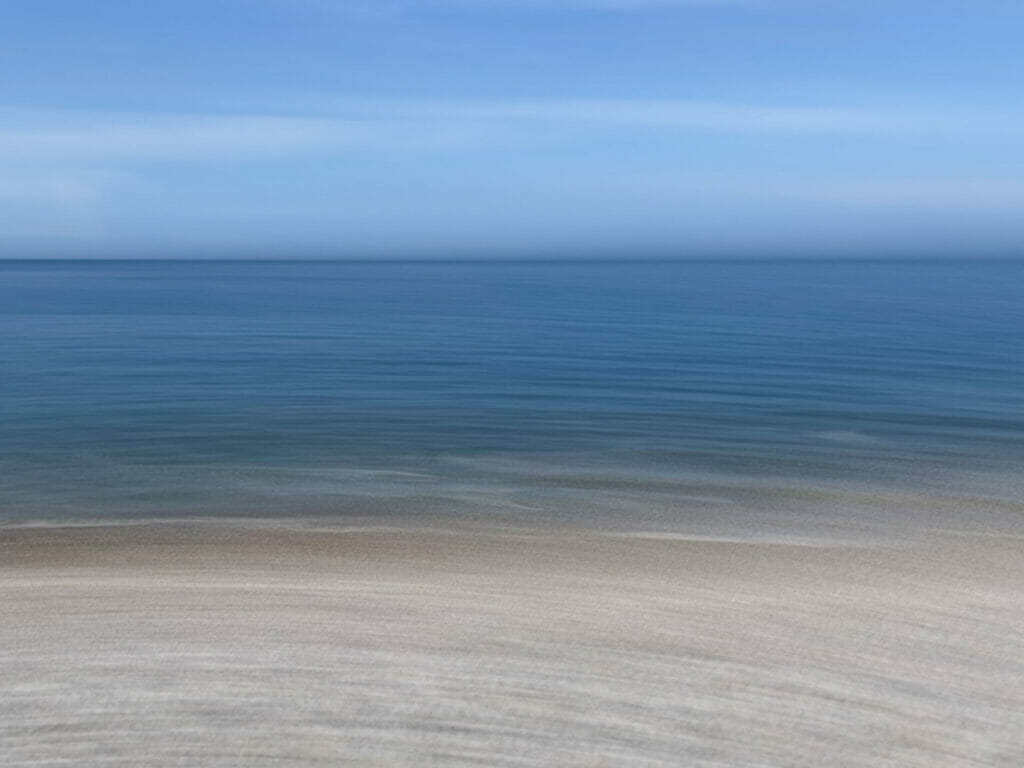 A blurred image of sand, sea and sky on the Llandudno Beach in North Wales