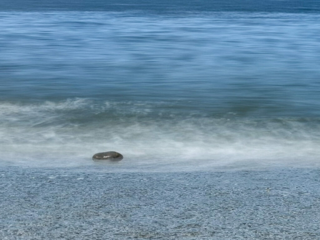 A blurred photo of sand, sea and blue sky in Llandudno showing a rock with small waves washing over it.