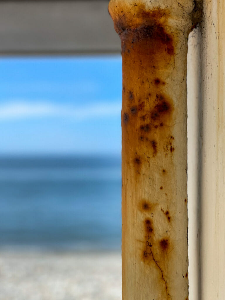 A photo looking through a window of a shelter on the Llandudno prom in North Wales looking toward the blue sea and sky