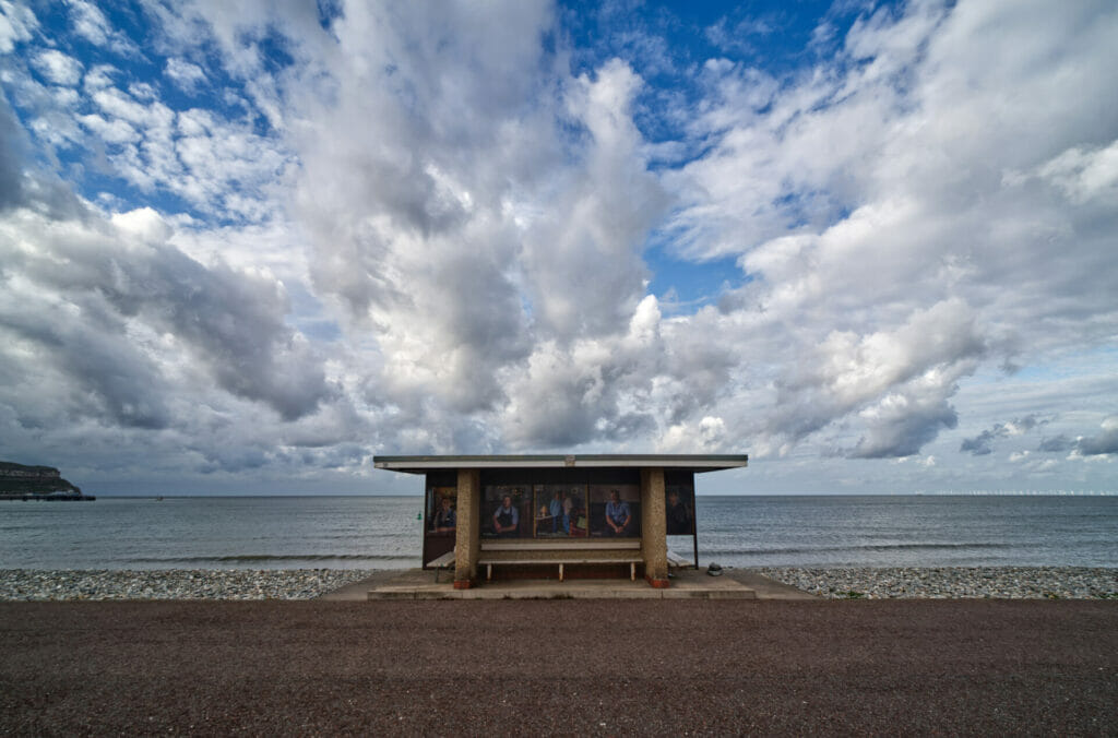 Photograph of a dramatic blue sky and white clouds above a shelter on the Llandudno prom in North Wales with photographic images of people working in hospitality which is part of a project.  Photo taken on a Taken on a Welshot Photographic Workshops and Events
