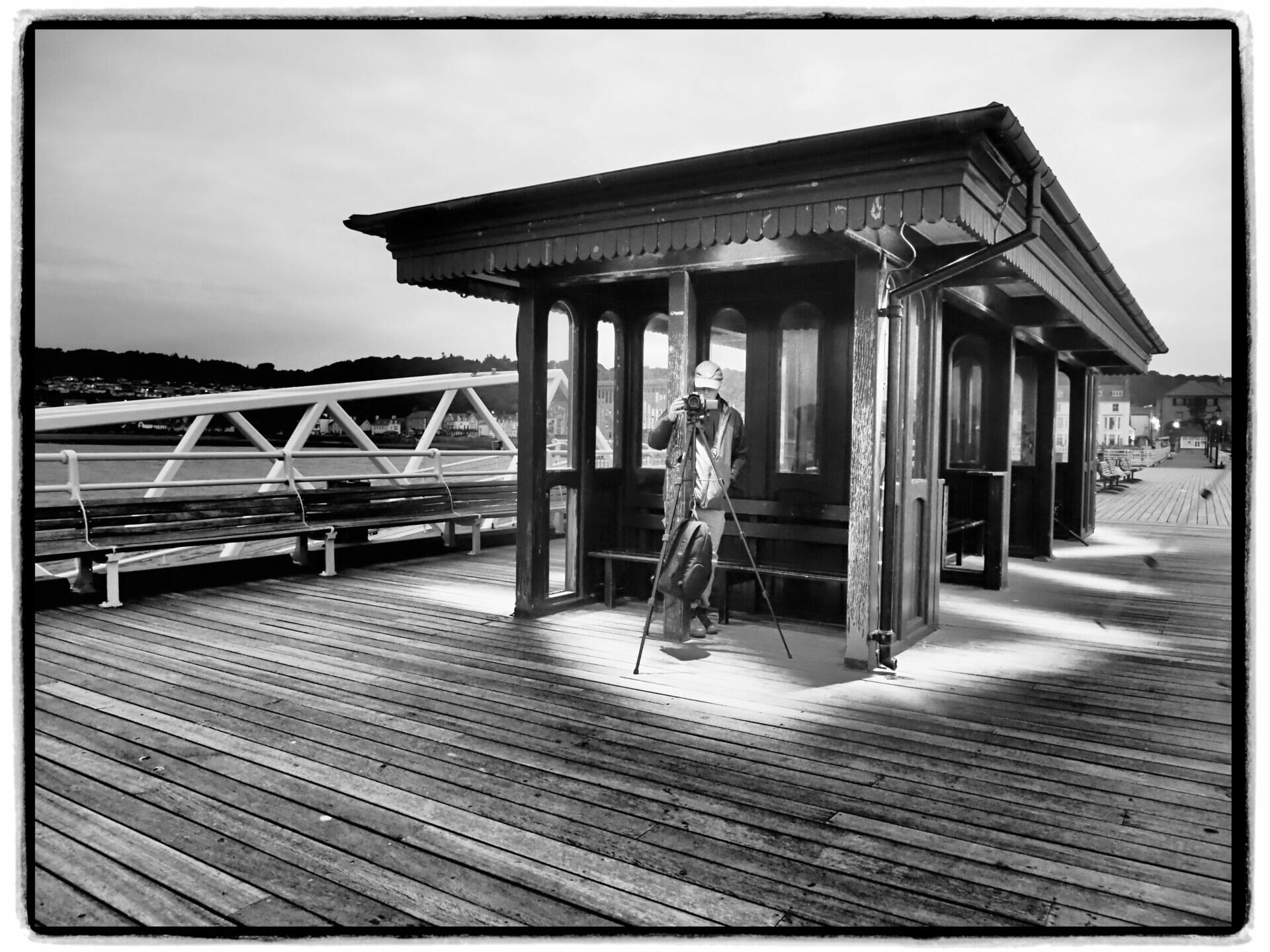 Black and White Photo of the shelter on Beaumaris Pier on Anglesey with a photographer taking a photo on a Welshot Photographic Workshop