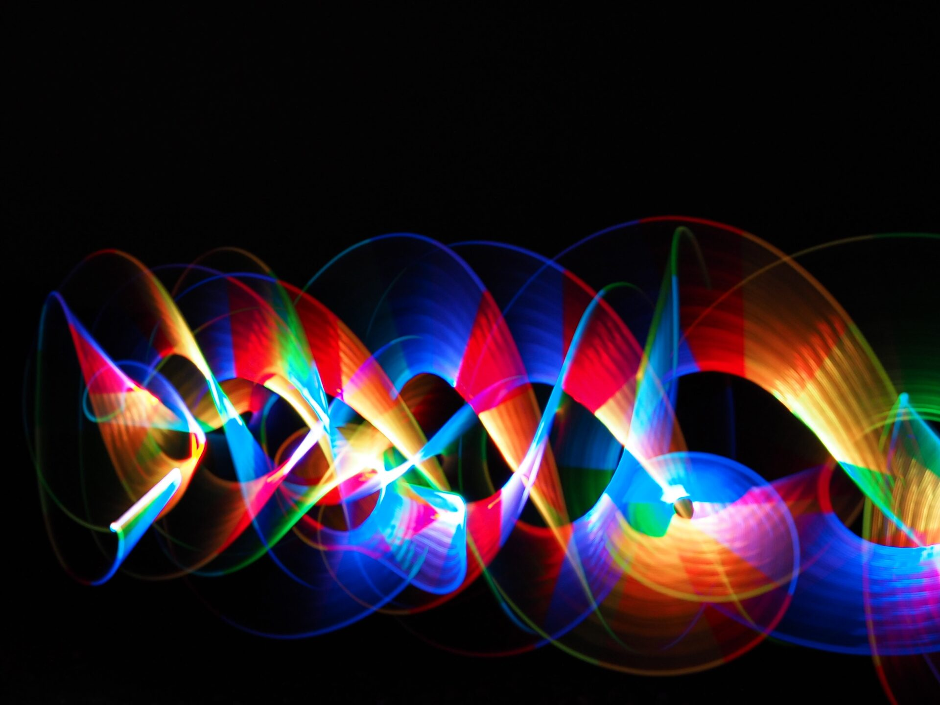 Long exposure photo of coloured lights being waved about on a Welshot Light Painting workshop on Anglesey, North Wales