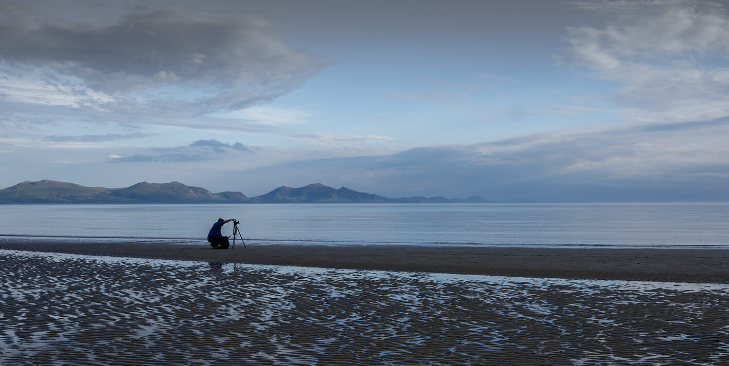 Photo of a lone photographer with a tripod taking a seascape and long exposure on Newborough beach on Anglesey