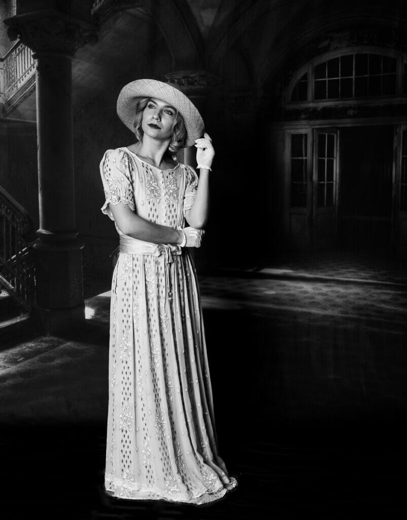 Black and White Photo of a Model wearing authentic costume in the style of Downton Abbey - Posing in front of a backdrop for the Mains Studio Flash Photography Welshot Academy Evening