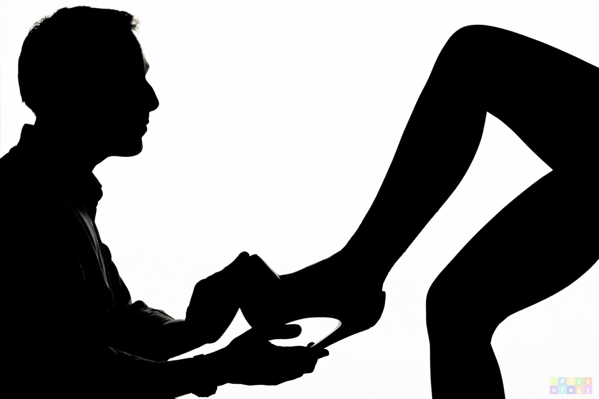 Black and White Photo showing a Silhouette of a Man putting a show on a ladies foot - taken at the Macro, Shape, Form & Texture Photography - Anglesey Photographic Academy Evening