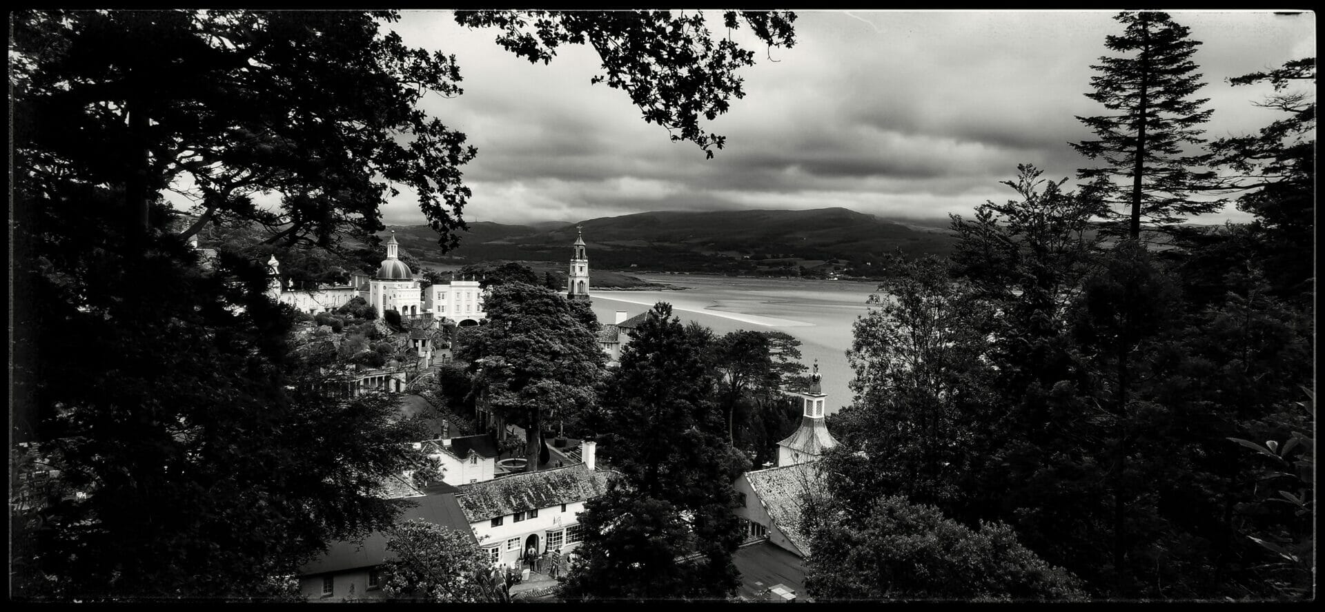 Black and White Photo of the Portmeirion Village in North Wales taken from a hillside viewpoint overlooking the estuary.