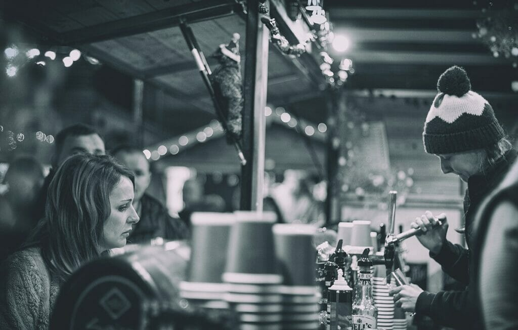 Black and White Photo of someone serving drinks at the Chester Christmas Markets