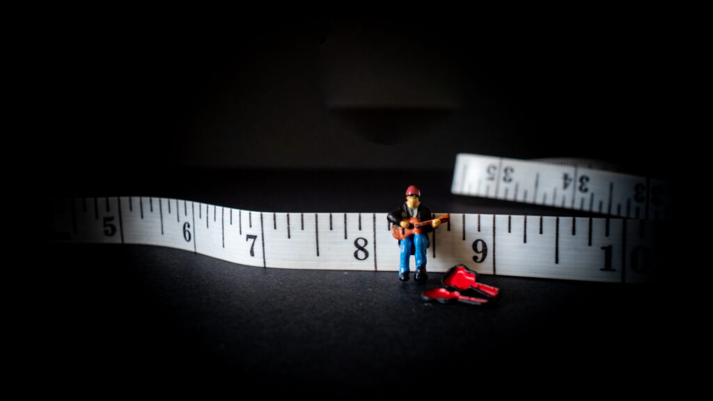 Creative photo showing a miniature model person playing a guitar on a tape measure.