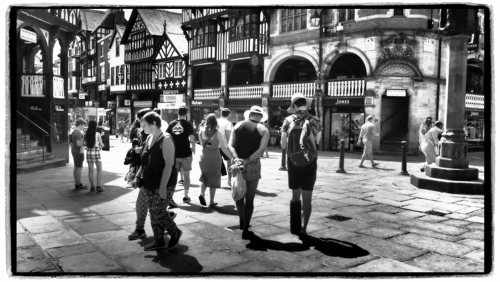 Black and White Photo of a group of people in the streets of Chester. The photos was taken on the Chester Walls - A Photographic Adventure with Welshot