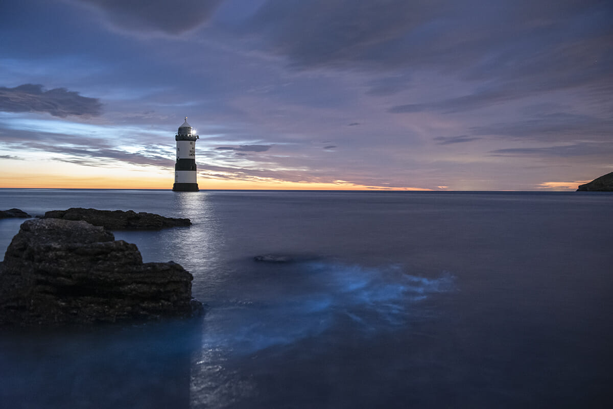 Colour Photo of Lighthouse at Penmon Point Anglesey with Bioluminescent in the sea - Taken on the Shortest Night Photographic Adventure with Welshot Imaging Photographic Academy